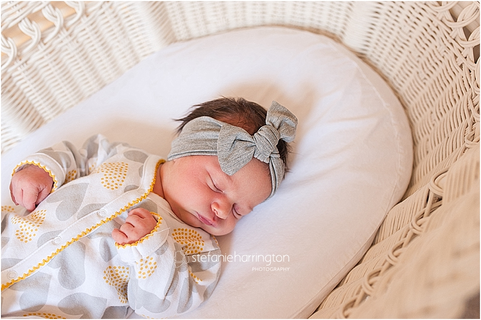 tiny newborn is sleeping in whicker bassinet