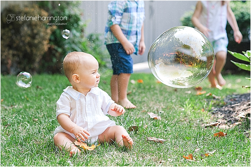 baby brother is surprised by a soap bubble bursting in front of his face
