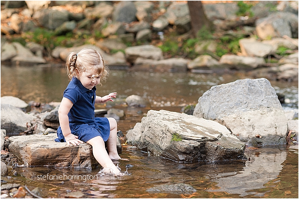 toddler girl in an adorable shirt dress is splashing in the water