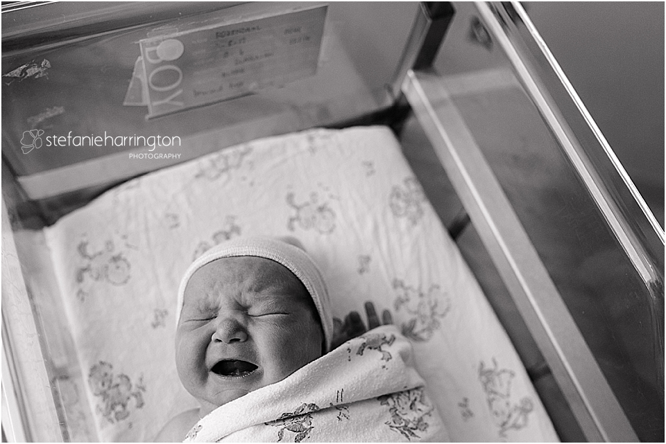 newborn baby is crying in the hospital bassinet